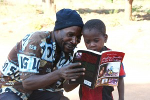 "A father who was in one of the photos in the book: ""Satisfying Zambian Hunger for Culture"" shows his son. This was at Chikana Village in Chief Magozi's area West of Lundazi in November 2012."