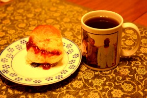 Drinking a cup of black sweetened tea with a scone or bun with jam in a Christmas special treat.