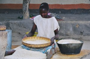 Girl using Chihengo or winning pounded maize in a village. Compose a poem about this in a Zambian language.